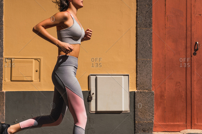 Side view of crop sportswoman in gray clothes jogging at old building on sunny street