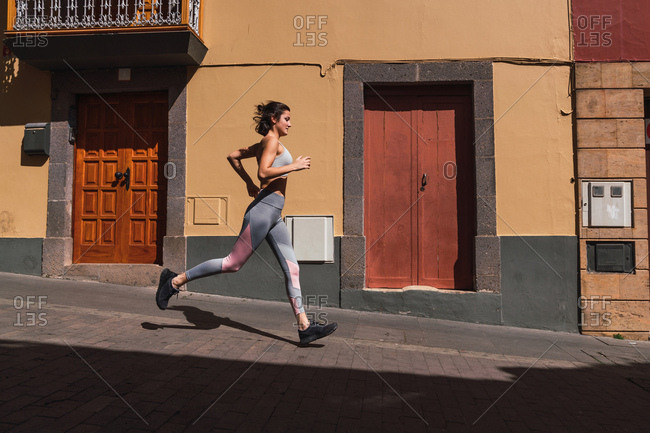 Side view of fit sportswoman running fast down the street on sunny day