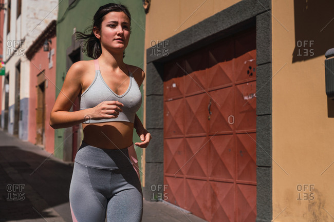 Attractive fit woman in gray sportswear jogging down the street in city on sunny day