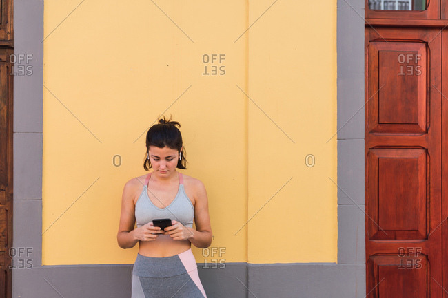 Concentrated fit woman in sportswear standing on city street and browsing phone