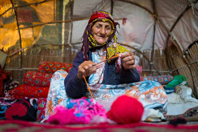 Old woman living in tent and making clothes