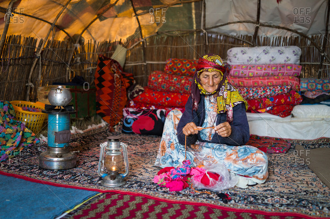 Old woman in tent and making clothes