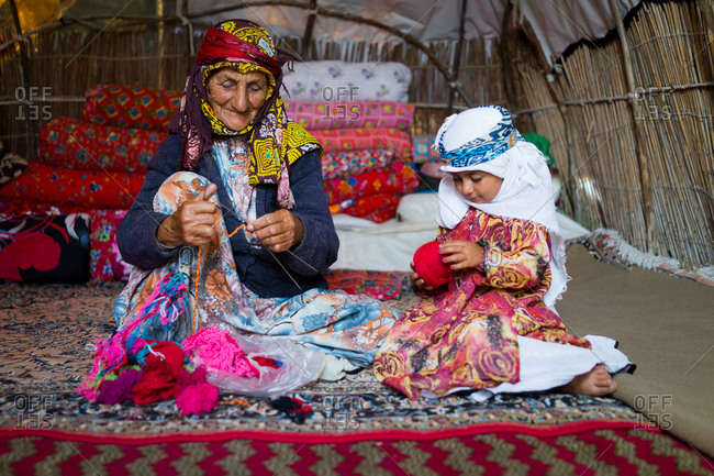 Old woman and her granddaughter in tent knitting