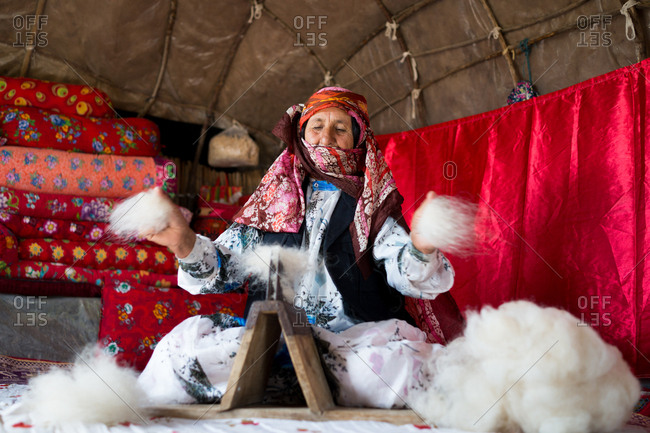 Old woman working with wool in her tent