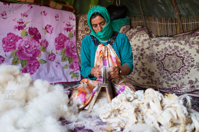 Woman working with wool at tent