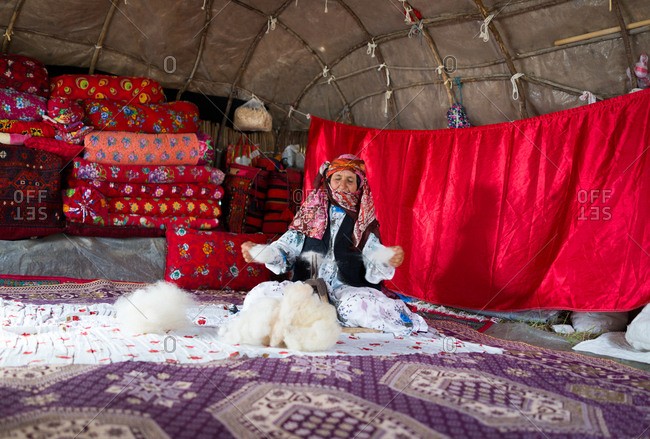 Elderly woman is working with wool in a tent