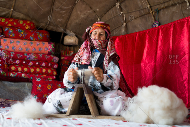 Old woman is working with wool in a tent