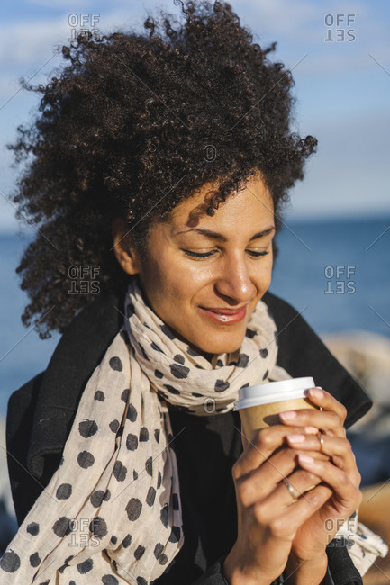 Portrait of smiling woman enjoying coffee to go near the sea