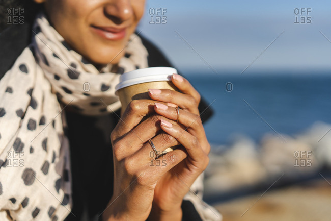 Woman's hands holding coffee to go- close-up