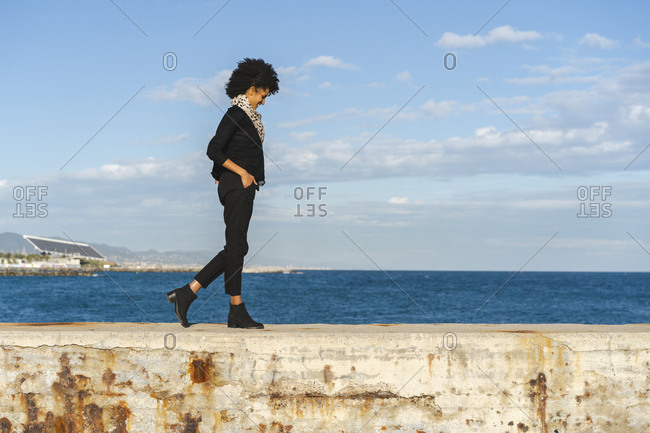 Spain- Barcelona- laughing woman dressed in black walking on wall at sunlight