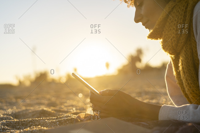Woman lying in the sand- relaxing on the  beach- reading an e-book