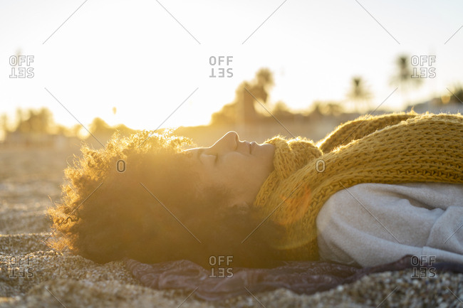 Woman lying in the sand- relaxing on the  beach