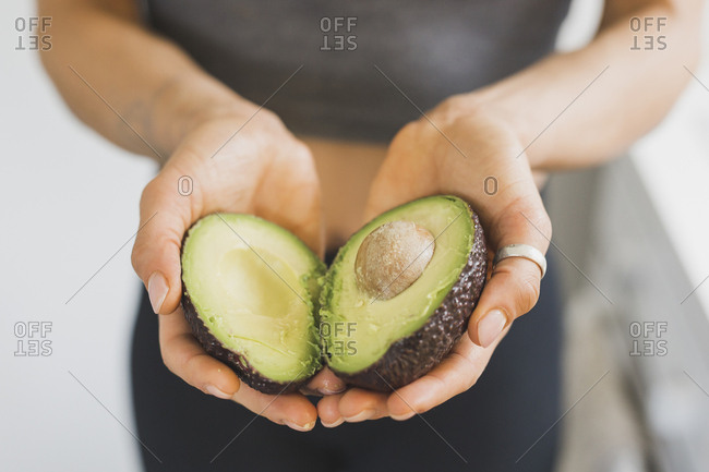 Hands of woman holding halved avocado