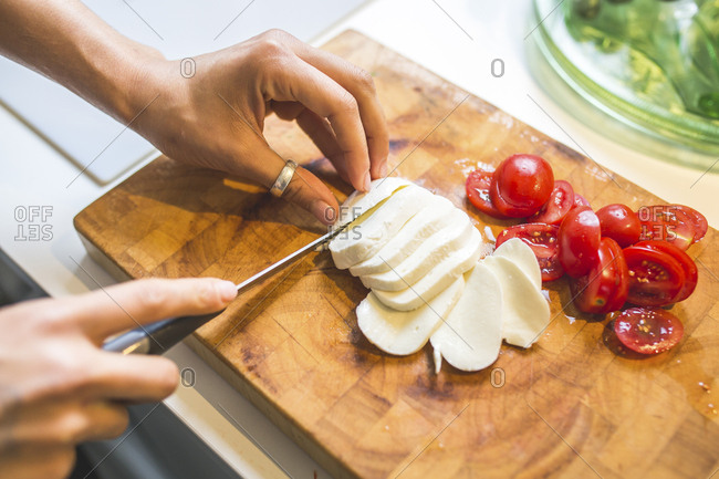 Woman preparing Caprese salad on chopping board