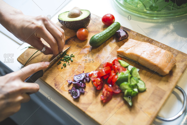 Woman preparing vegetables and salmon on chopping board