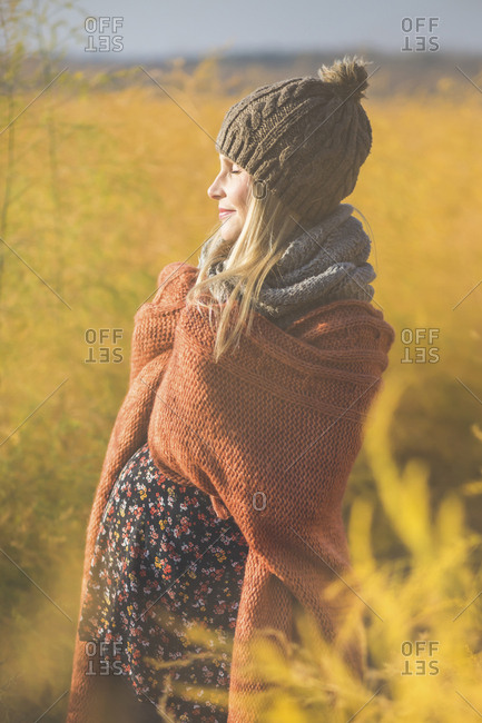 Smiling pregnant woman with closed eyes enjoying the sunshine