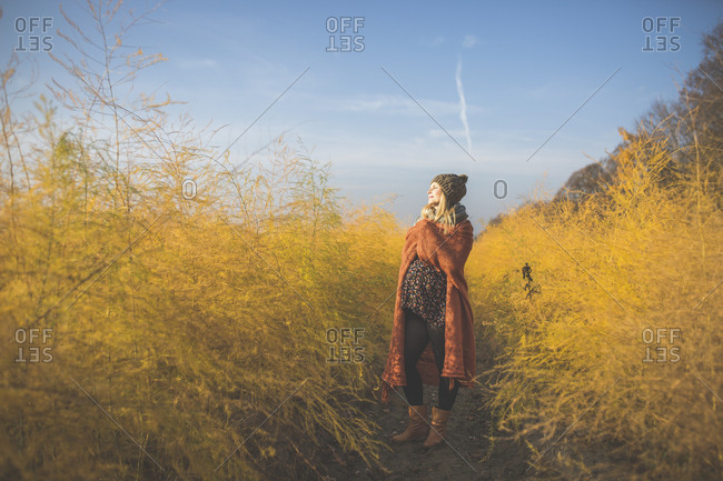 Pregnant woman standing in asparagus field in autumn