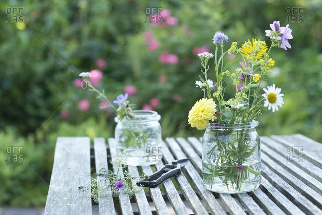 Wildflowers in preserving jars on garden table