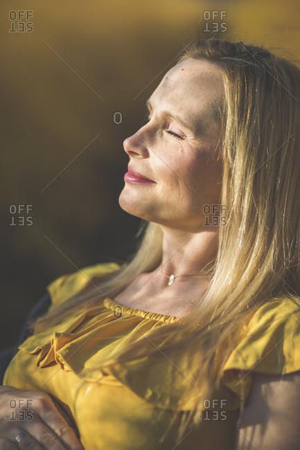 Smiling woman with closed eyes enjoying the sunshine