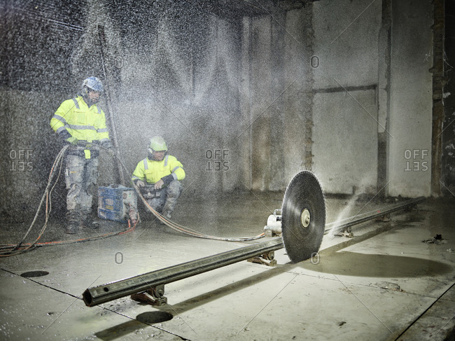 Construction workers sawing with a concrete saw