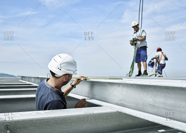Construction worker checking steel girder