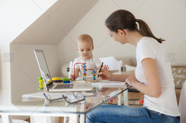 Mother using laptop and little daughter playing at table at home