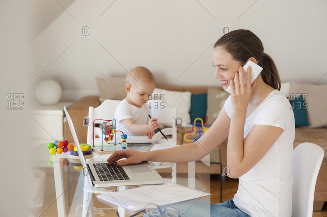 Smiling mother using laptop and cell phone with little daughter playing at table at home