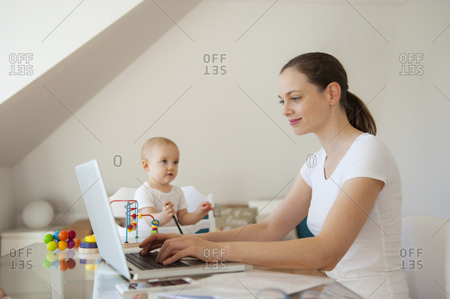 Smiling mother using laptop and little daughter playing at table at home