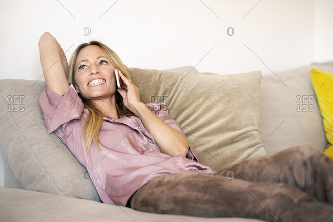 Portrait of woman on the phone relaxing on the couch at home