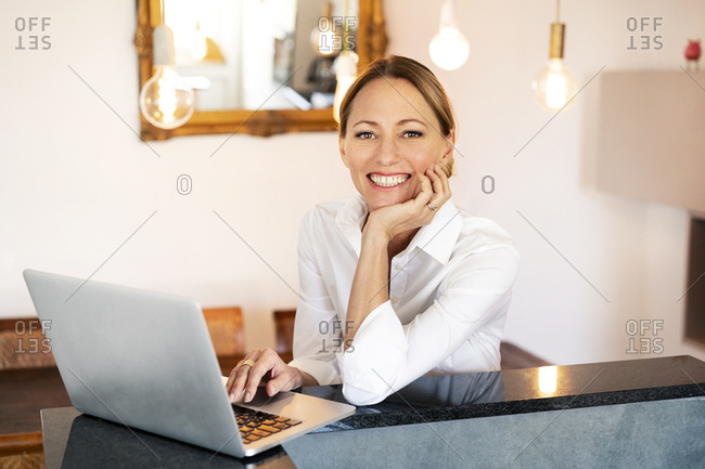 Portrait of smiling businesswoman with laptop at home office
