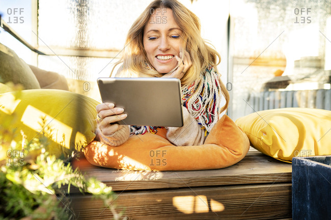 Portrait of smiling blond mature woman relaxing in winter garden using digital tablet