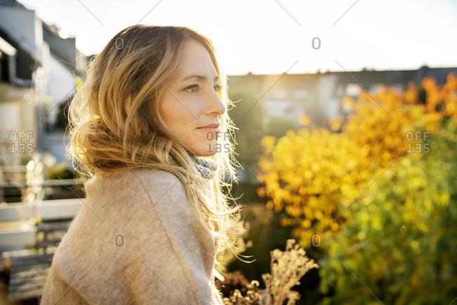 Blond mature woman enjoying sunny autumnal day on balcony
