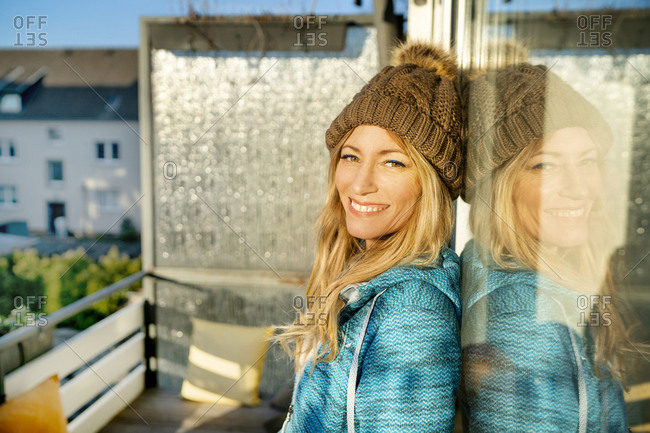 Portrait of smiling blond mature woman wearing bobble hat on balcony