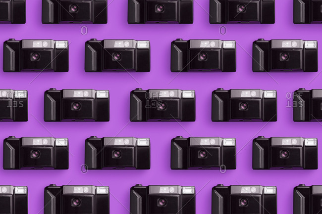 Plastic photo cameras organized in a row over pink background