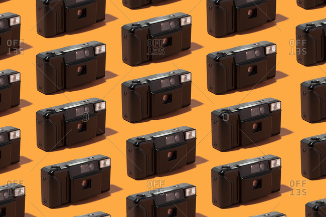 Plastic photo cameras organized in a row over orange background
