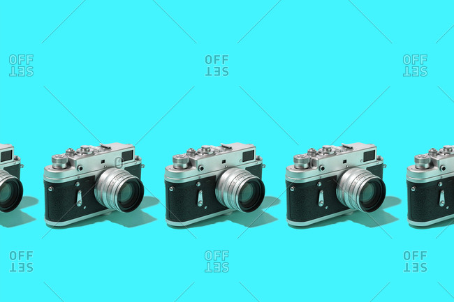 Photo cameras organized in a row over blue background