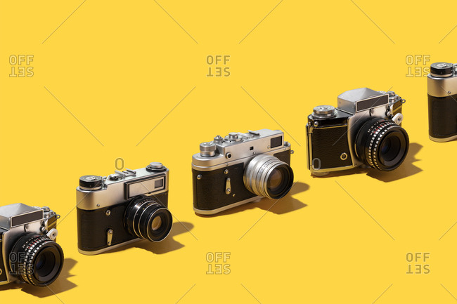 Photo cameras organized in a row over yellow background
