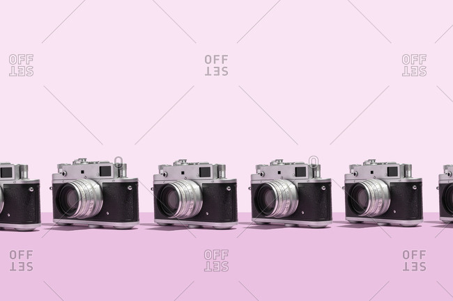 Photo cameras organized in a row over pink background