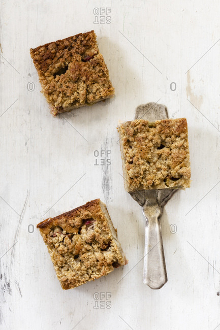 Three pieces of rhubarb cake and a cake server on white wood