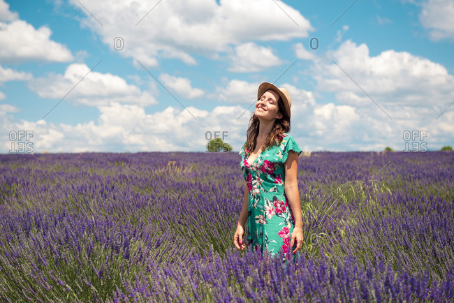 France- Provence- Valensole plateau- happy woman with straw hat standning in lavender field