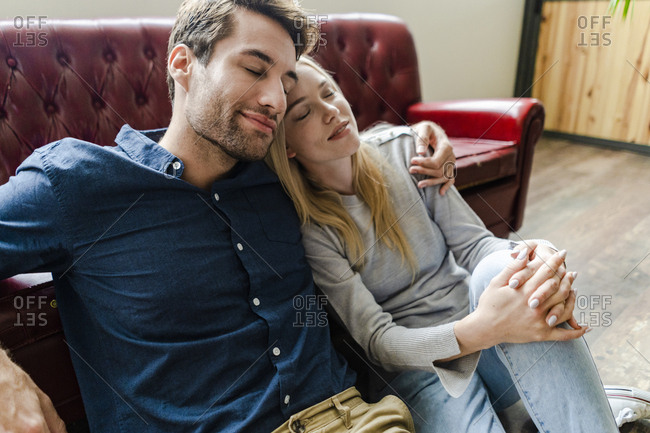Smiling young couple with closed eyes sitting on the floor embracing