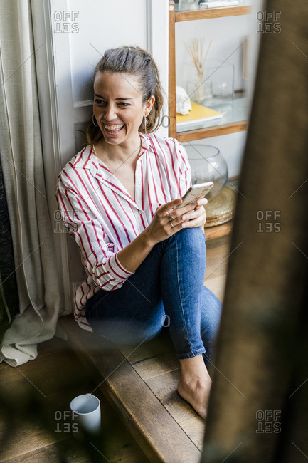Laughing woman sitting on the floor at home with cell phone