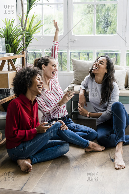 Three carefree women sitting on the floor at home with cell phones