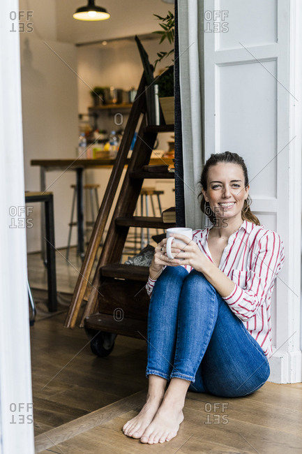 Portrait of smiling woman sitting on the floor at home with cup of coffee