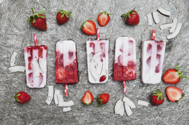 Homemade strawberry coconut ice lollies with fresh strawberries and coconut slices on granite