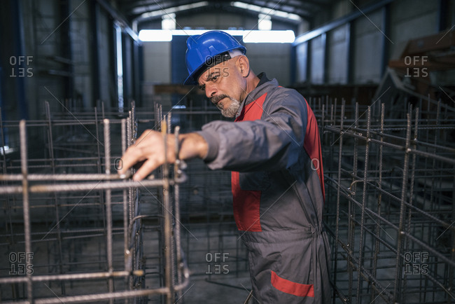 Worker wearing hard hat in factory checking rebar
