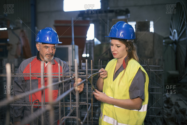 Male and female worker wearing hard hats working on rebar in factory