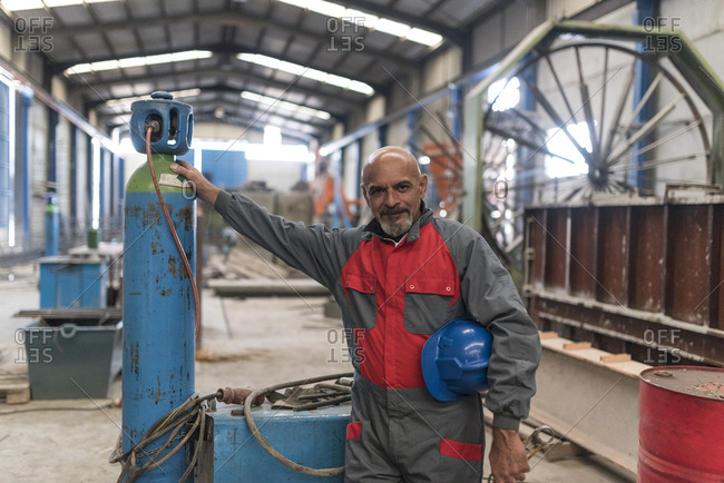 Portrait of confident worker standing next to a compressor in factory