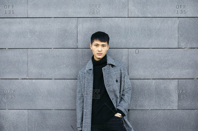 Portrait of stylish young man wearing black turtleneck pullover and grey coat