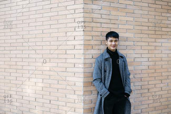 Portrait of smiling young man wearing grey coat and black turtleneck pullover leaning against wall